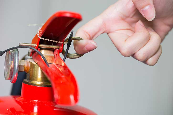 Pulling safety pin on fire extinguisher